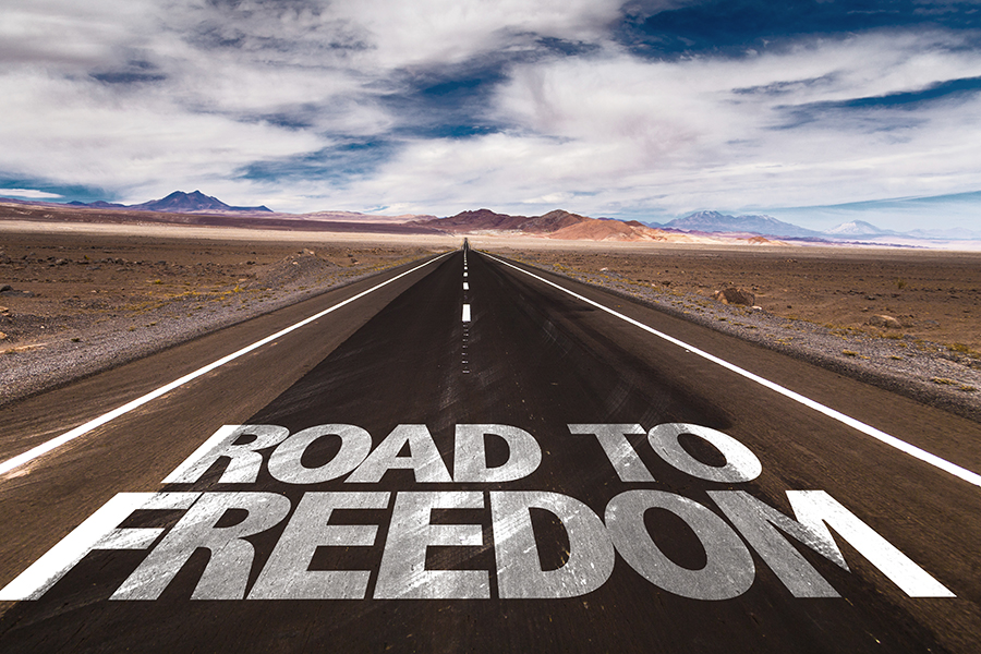 Road to Freedom written on desert road